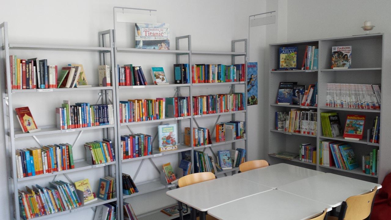 Bücherei der Janusz-Korczak-Schule Aachen mit vielen Büchern und einem Tisch im Bild